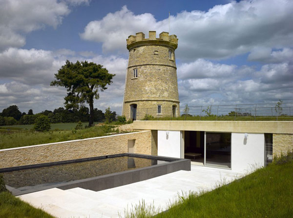 Круглая башня в Глостершире и современное строение рядом с ней.
